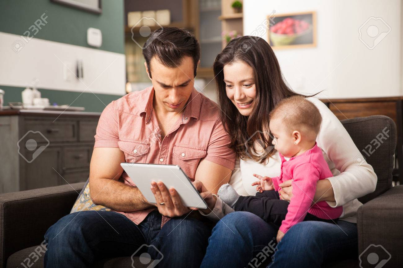Bonne Recherche Jeunes Parents Montrant Des Jeux Et Des Dessins Animés À  Leur Bébé Fille Sur Un Ordinateur Tablette dedans Recherche De Jeux De Fille