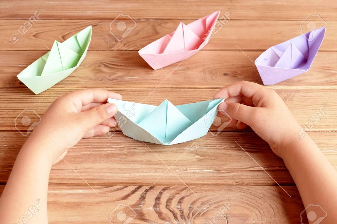 Enfant Détient Le Navire De L'origami Dans Ses Mains. Navires Colorés  Papier Origami Pliage Sur Une Table En Bois. Préscolaire Et Papier De  Maternelle à Pliage Papier Enfant