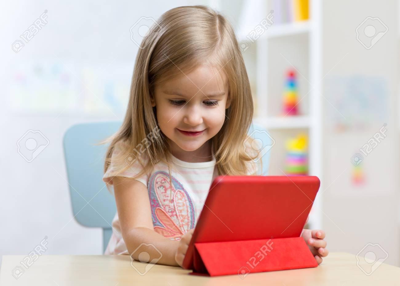 Enfant Fille Avec Ordinateur Tablette À Table À La Maison. à Tablette Enfant Fille