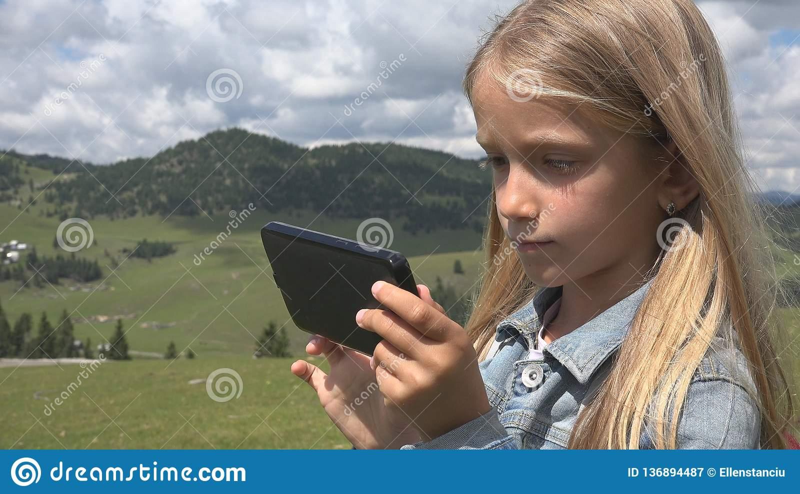 Enfant Jouant La Tablette Extérieure En Parc, Utilisation concernant Tablette Enfant Fille
