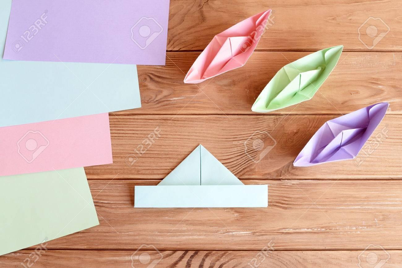 Ensemble De Bateaux Origami Et Feuilles Carrées De Papier Coloré Sur Une  Table En Bois. Comment Faire Un Simple Navire Origami. Tutoriel De Pliage serapportantà Pliage Papier Enfant