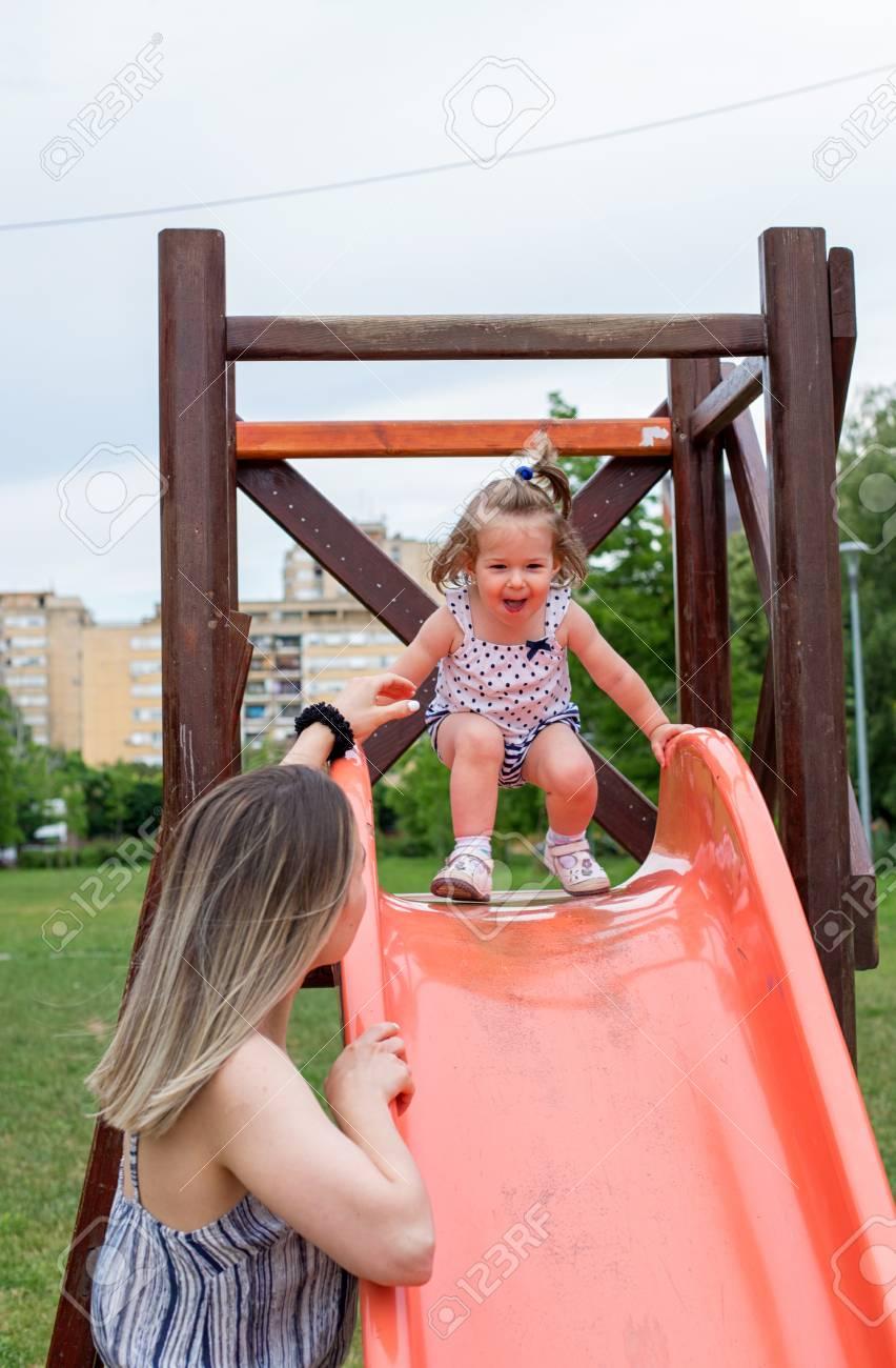 Heureuse Petite Fille Sur La Diapositive À L'aire De Jeux Pour Enfants à Jeux Pour Petite Fille