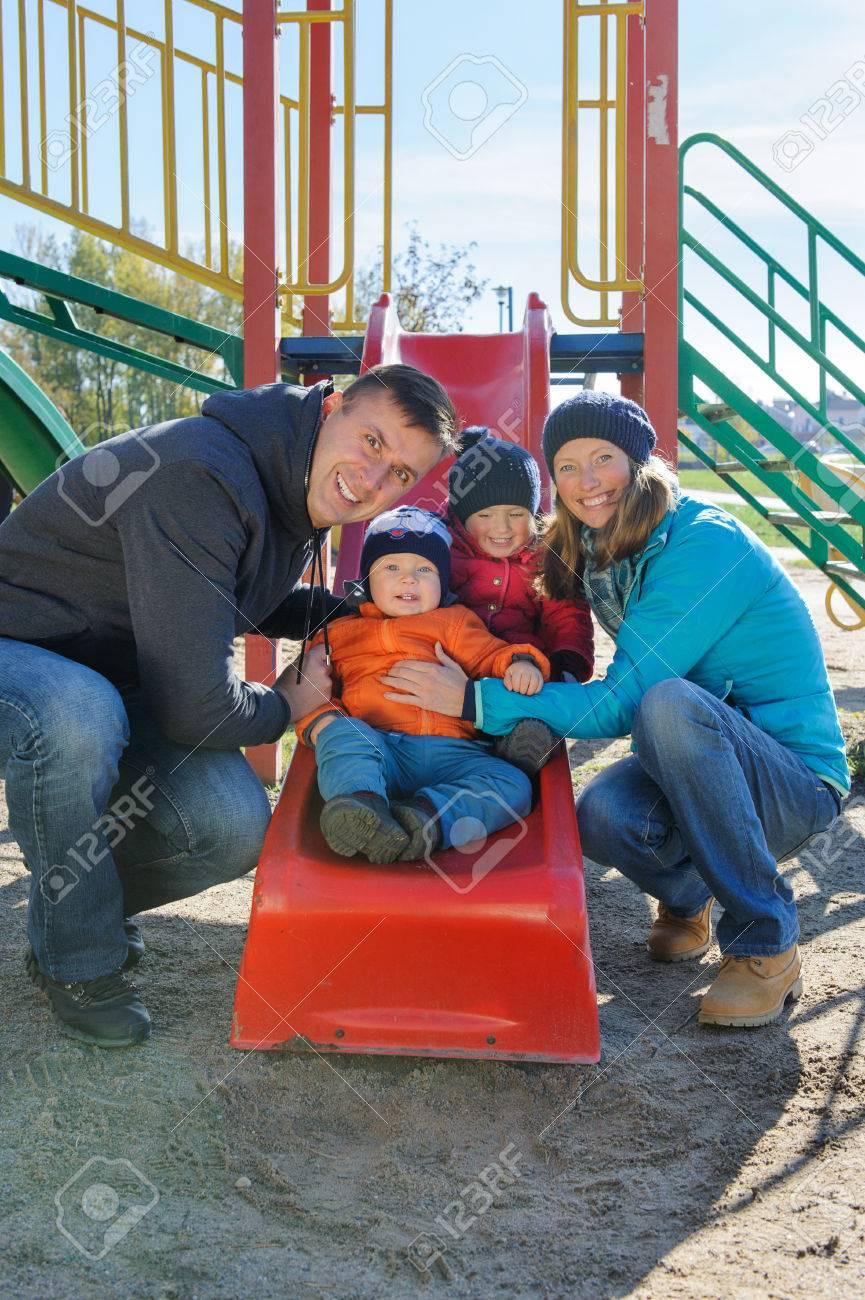 Heureuse Souriante Jeune Famille De Quatre Personnes À L'aire De Jeux Pour  Enfants Dans Le Parc serapportantà Jeux Pour Jeunes Enfants