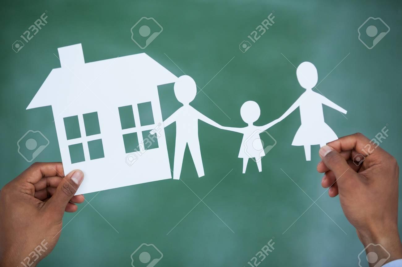 Homme Tenant Papier Découper Famille Et Maison Sur Fond Vert encequiconcerne Maison Papier A Decouper