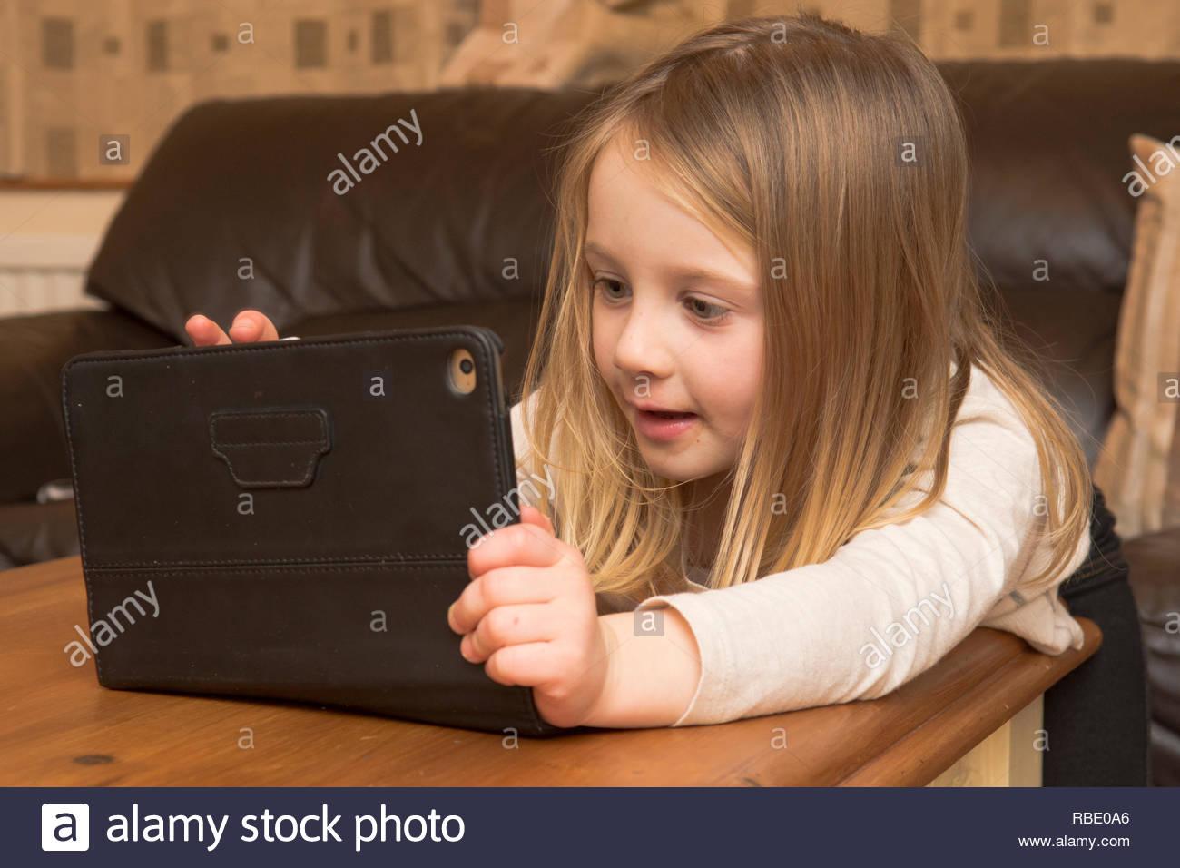 Jeune Fille Jouant Avec Un Appareil Numérique, Tablette intérieur Tablette Enfant Fille