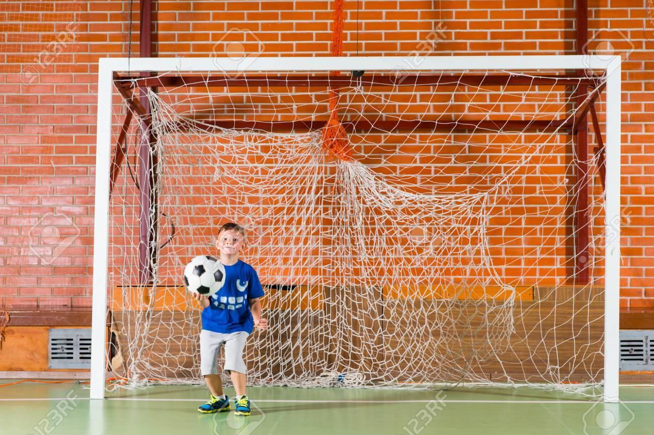 Jeune Garçon Jouant Gardien De But Pour Un Jeu De Soccer Intérieur En  Tenant Le Ballon Dans Sa Main Comme Il Regarde Les Joueurs à Jeux De Gardien De But