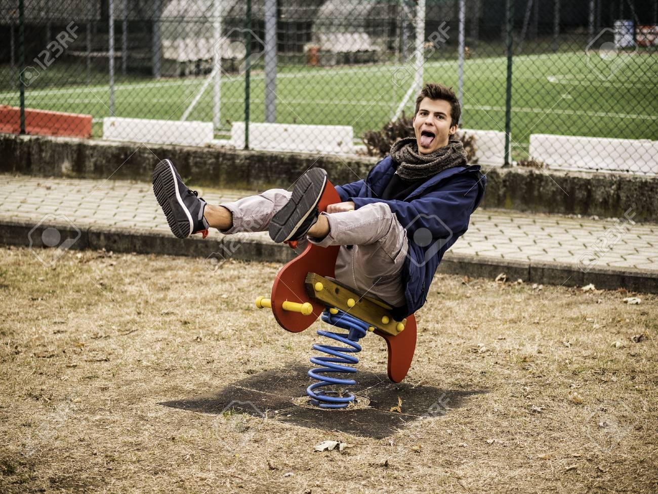 Jeune Homme Revivant Son Enfance Dans Une Aire De Jeux Pour Enfants À  Cheval Sur Un Siège De Printemps Rouge Coloré Avec Un Sourire Heureux Dans  Un avec Jeux Pour Jeunes Enfants