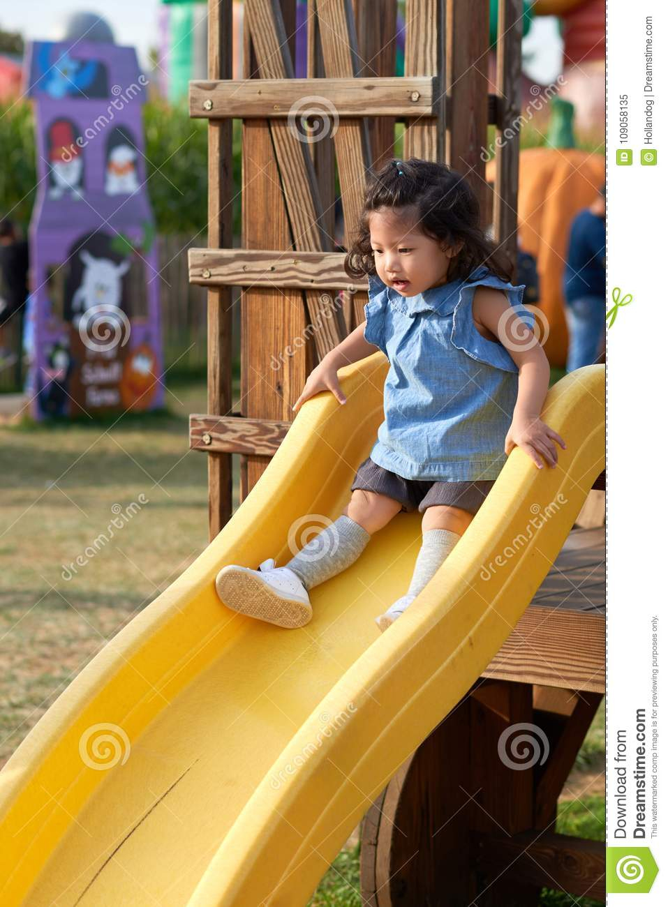 Le Bébé Asiatique Va Vers Le Bas Sur Une Glissière Dans Le dedans Jeux Pour Bebe Gratuit
