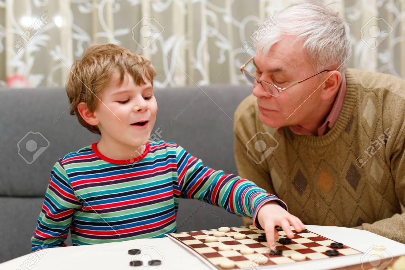 Petit Enfant Garçon Et Grand-Père Supérieur Jouer Ensemble Jeu De Dames dedans Jeux De Grand Garçon