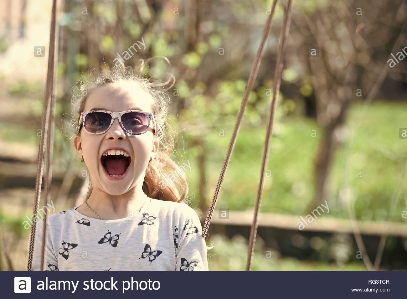 Petit Enfant Sourire Sur Swing En Cour D'été. Fashion Girl avec Jeux Pour Petit Enfant