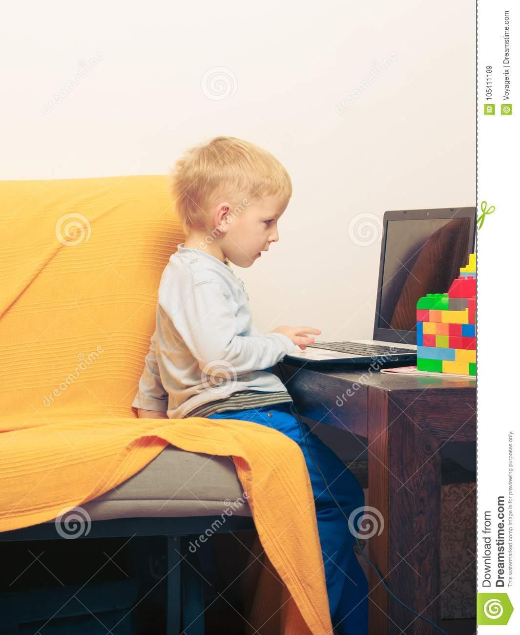 Petit Garçon À L'aide De L'ordinateur Portable Jouant Des à Jeux Gratuit Garcon