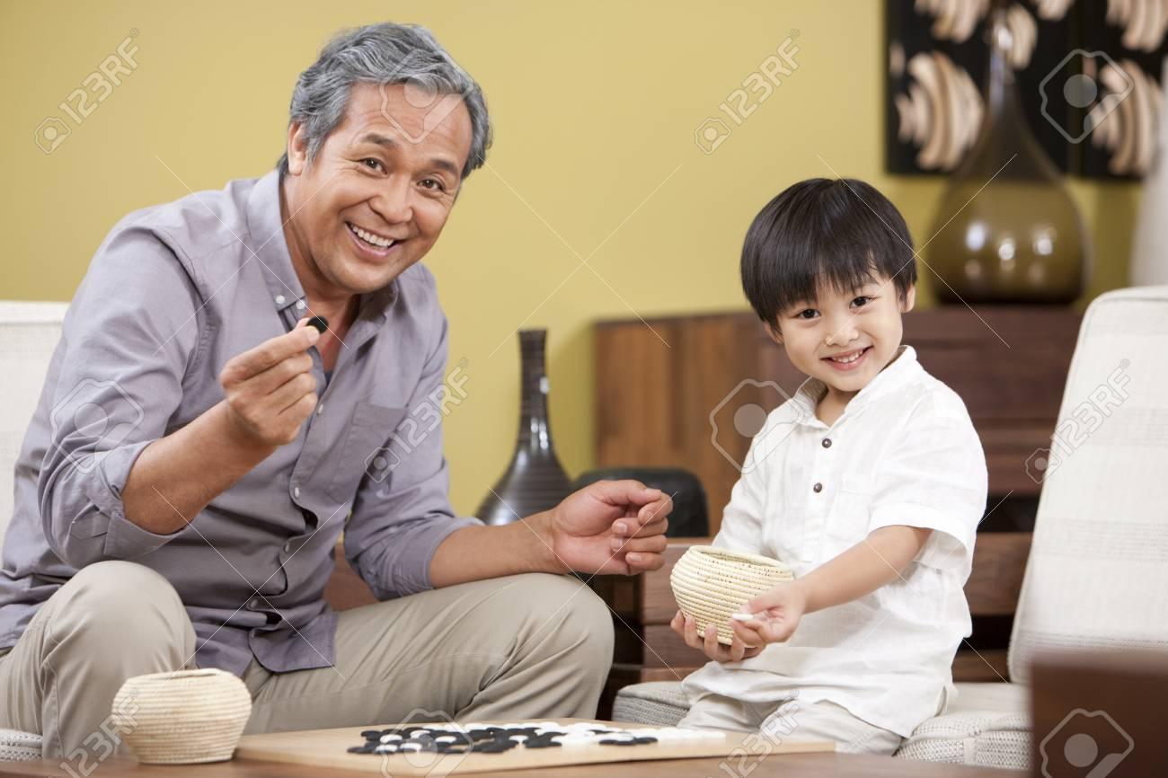 Petit Garçon Jouant Au Jeu Chinois De Go Avec Grand-Père avec Jeux De Grand Garçon