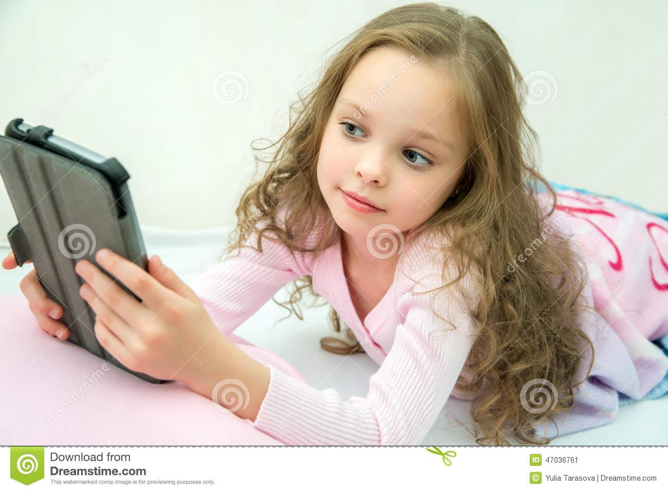 Petite Fille Heureuse Se Trouvant Sur Le Lit Avec La avec Tablette Enfant Fille