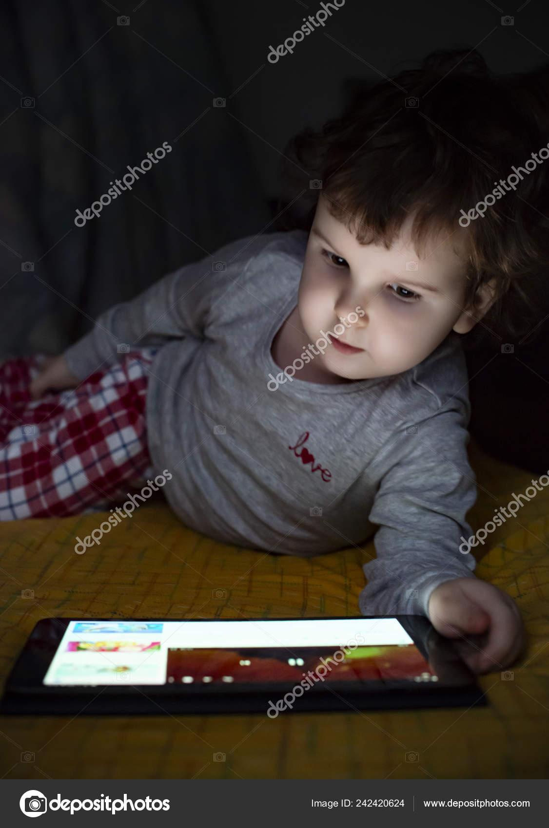 Petite Fille Regardant Tablette Dans Lit Illuminé Visage tout Tablette Enfant Fille