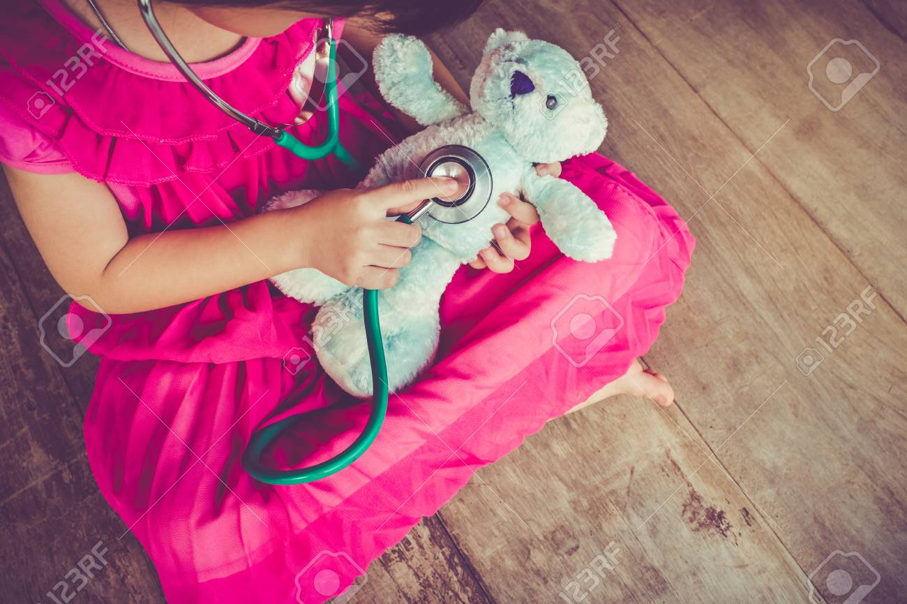 Vue De Dessus Enfant Jouant Médecin Ou Une Infirmière Avec Un Ours En  Peluche Avec La Lumière Du Soleil À La Maison. Bonne Fille Écoute Un  Stéthoscope avec Jeux Ludique Enfant