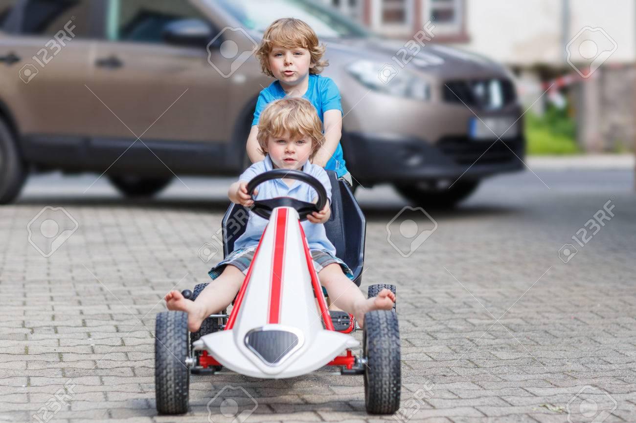 Deux Amis Heureux Petit Garçon Amusant Avec Voiture De Course De Jouets  Dans Le Jardin D'été, À L'extérieur. Kid Active Pousser La Voiture Avec Son dedans Plein De Jeux De Voiture