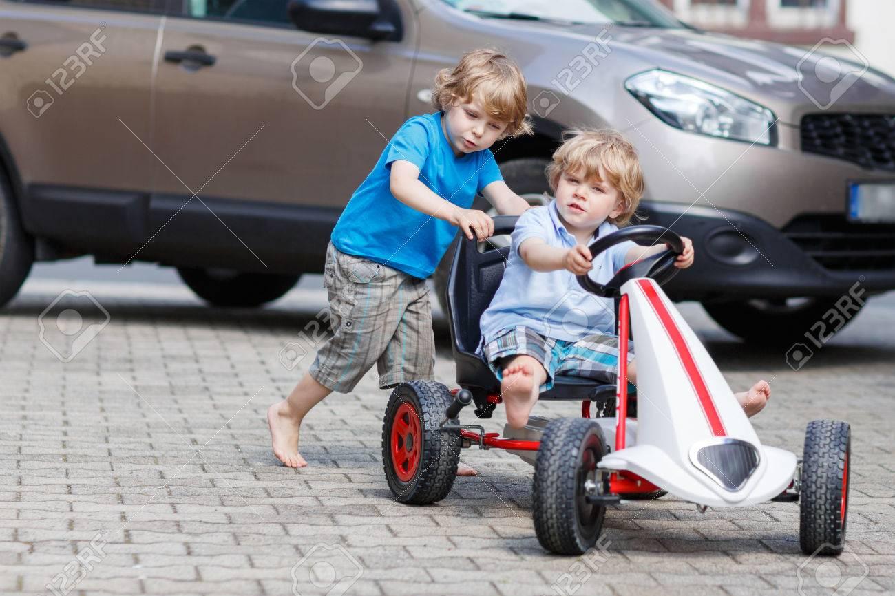 Deux Enfants Heureux Amuser Avec Voiture De Course De Jouets Dans Le Jardin  D'été, À L'extérieur. Frère Active Pousser La Voiture Avec Son Jeune dedans Plein De Jeux De Voiture