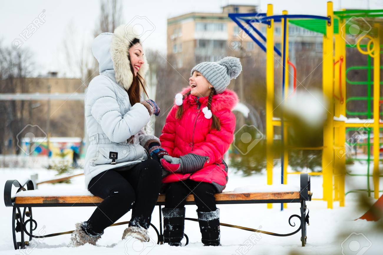 Deux Filles Heureuse, Mère Et Fille Assise Sur Un Banc Sur Une Aire De Jeux  Dans Le Parc De La Ville Au Jour D'hiver Glacial. encequiconcerne Jeux De Deux Fille