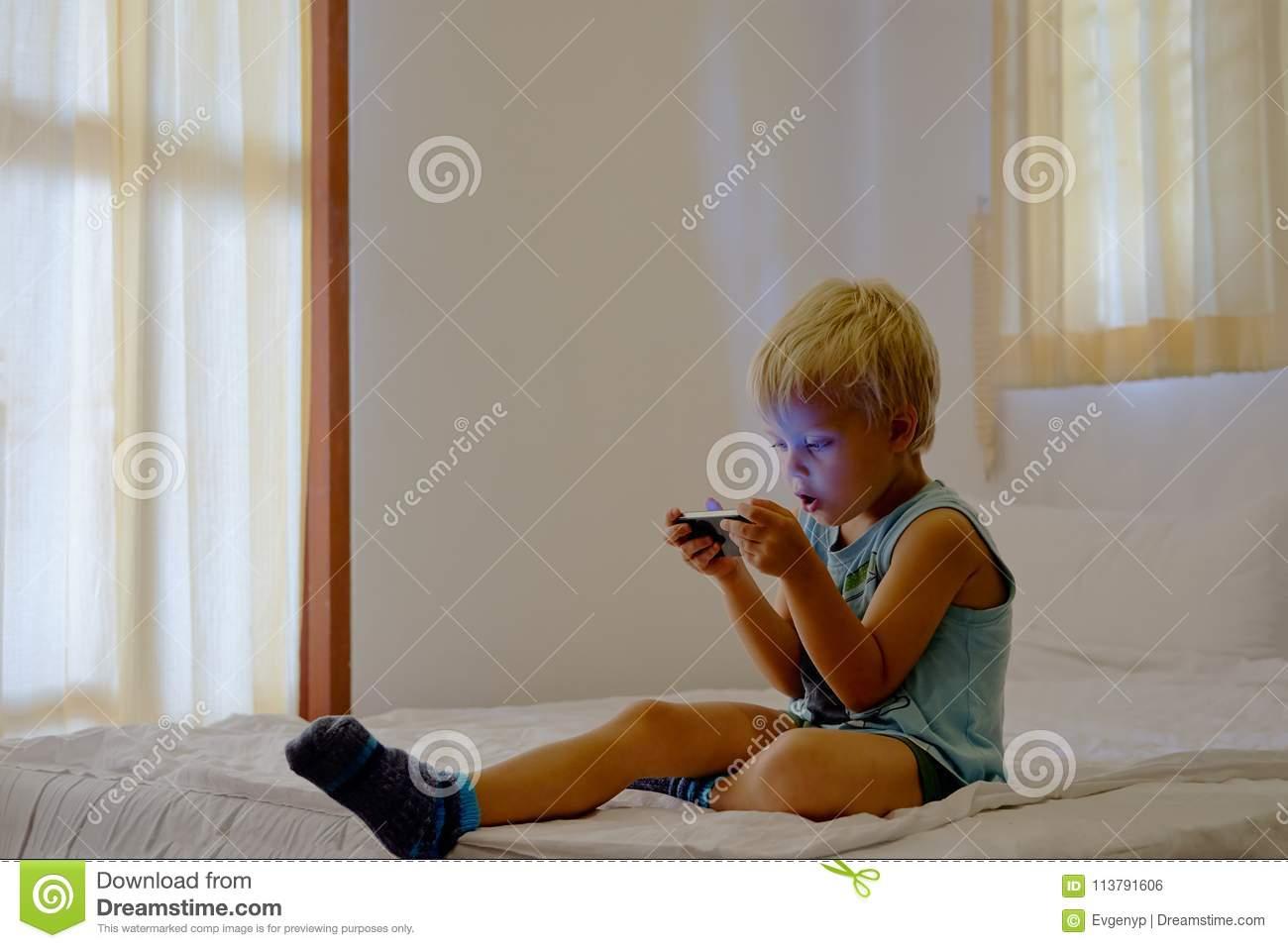 Garçon Jouant Des Jeux Vidéo Sur Le Dispositif Portatif avec Jeux De Vetement Pour Garçon