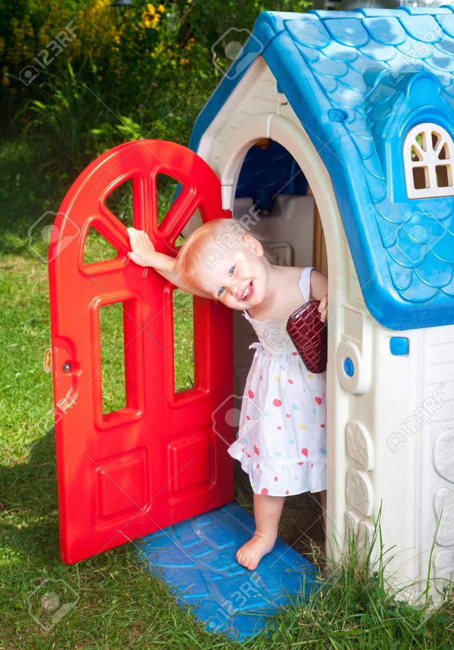 Petit Bébé Fille Portant Robe Blanche Regardant Plastique Maison De Jeu  Porte Dans Une Aire De Jeux D'été à Jeux Bebe Fille