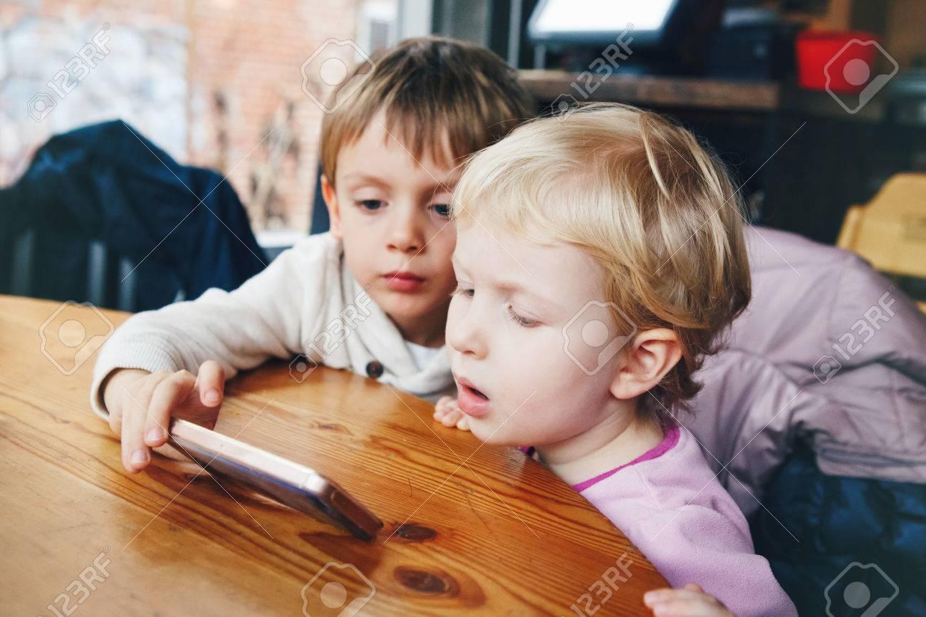 Portrait De Deux Enfants Tout-Petits Garçon Et Une Fille Jouant Téléphone  Cellulaire Jeux De Tablettes, Regarder Des Dessins Animés Film, Assis À avec Tout Les Jeux De Fille Et De Garcon