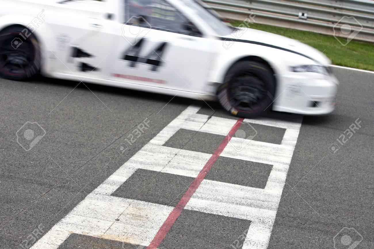 Voiture De Course De Franchir La Ligne D'arrivée Sur Un Circuit intérieur Course Voiture En Ligne