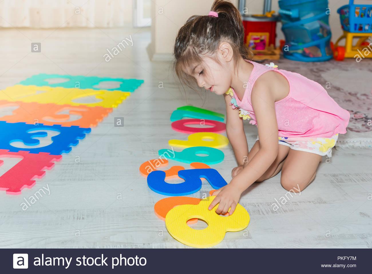 Vue Latérale D'une Mignonne Petite Fille Est Assise Et Tapis tout Jeux De Fille Puzzle
